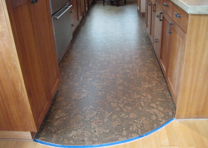 Pre-finished Cork flooring installed as a floating floor installation in kitchen galley with new baseboards