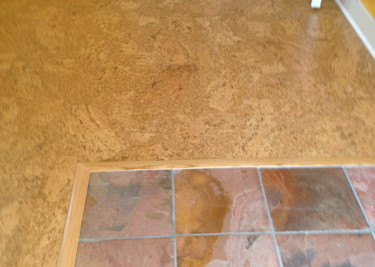 re-finished Cork flooring installed as a floating floor installation and trimmed around slate flooring and new baseboards