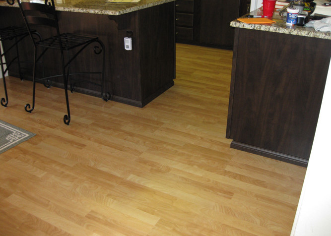 Laminate Plank Flooring as a floating installation in kitchendinning area with new baseboards