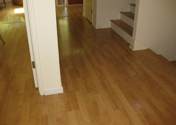 Laminate Plank Flooring as a floating installation in living area and stairway with painted riser