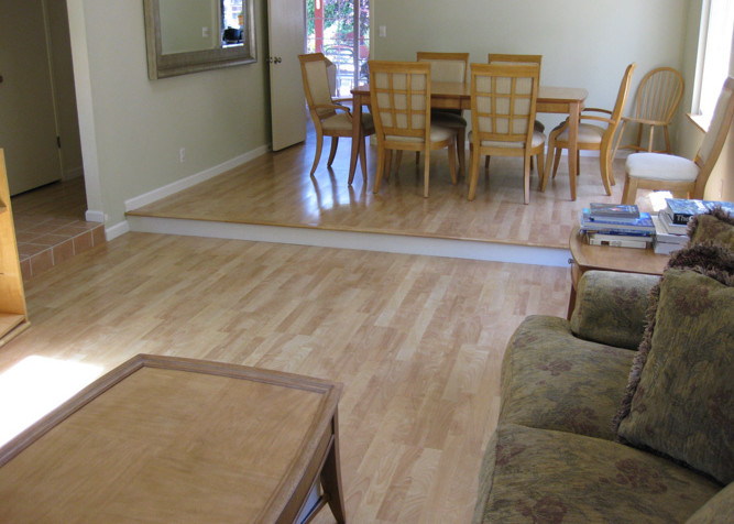 Laminate Plank Flooring as a floating installation in Living/Dinning room area with painted riser on step