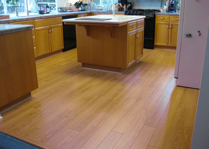 Laminate Plank Flooring as a floating installation in kitchen area with new baseboards