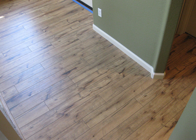 Laminate plank flooring installed as a floating floor installation with new baseboards in a entry and hall-half bath