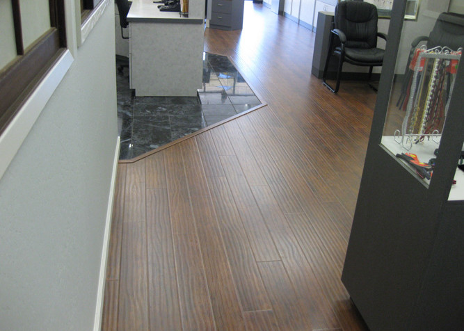 Laminate plank flooring installed as a floating floor installation with new baseboards in Optometrist showroom