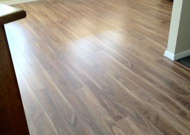Laminate plank flooring installed as a floating floor installation with new baseboards in Chiropractors lobby