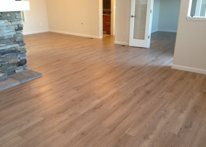Laminate Plank flooring install as a floating floor around rock fireplace in a manufactured home with new baseboards