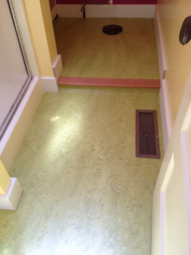 Marmoleum Sheet Flooring Install With Custom Step And New Baseboards On All Perimeter In A Bathroom