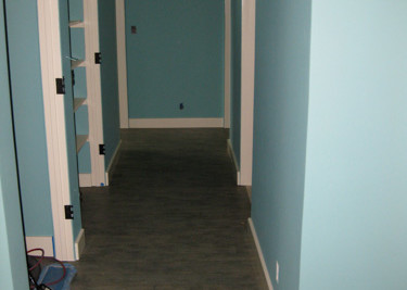 Vinyl sheet flooring installed as a flat-lay floor installation with new baseboards through out project site
