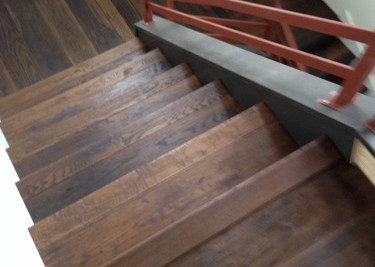 Wire brushed/oil pre-finished engineered random length plank wood flooring installed as a nail/glue down on staircase with printed black riser