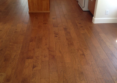 Pre-finished engineered plank wood flooring installed as a floating floor installation with new baseboard in kitchen area