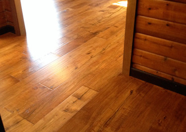 Pre-finished engineered plank wood flooring installed as a nail down installation with new baseboards in a log cabin living/dinning room