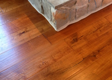 Pre-finished engineered plank flooring installed as a nail down installation around rock fireplace with new baseboard in log cabin living/dinning