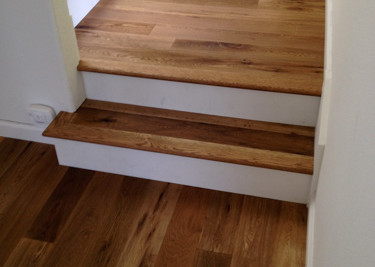 Pre-finished T&G engineered wood flooring installed on stairway with printed riser