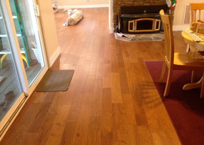 Engineered T&G Hickory pre-finished wood flooring as nail down installation with new baseboards.